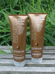 Two 8.5 oz bottles of shampoo & conditioner for color treated brown hair set in a green grassy background