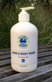 16 oz. bottle of unscented hand & body wash with pump, set on a green leafy background