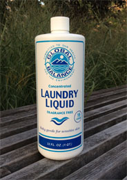 bottle of non-toxic laundry liquid detergent set on a green leafy background
