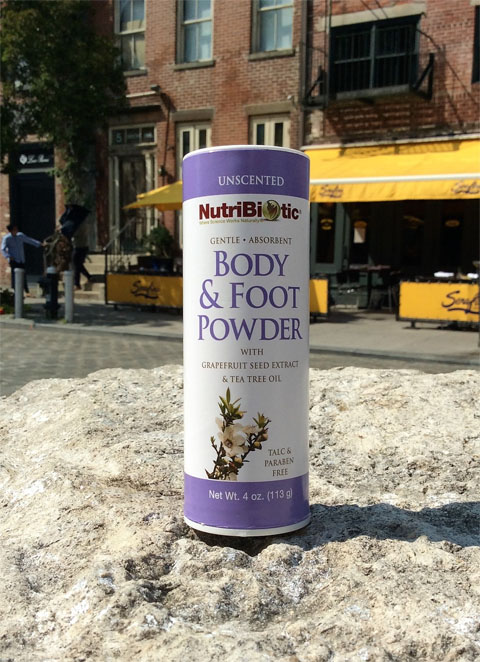 4 oz. container of body & foot powder with urban background